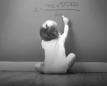 A child writing an equation on a wall
